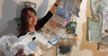 A woman holds a long roll of different pieces of paper glued together.