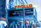 A view of the Apollo theater with a street vendor beside it.