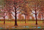 Autumnal trees in a park with puddles of water on the ground.