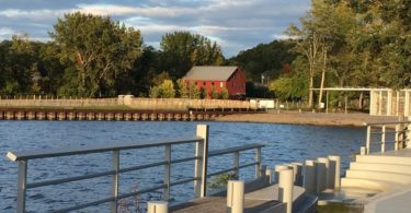A red house on the side of a body of water with trees surrounding it.