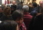 A large crowd of people in a gallery.