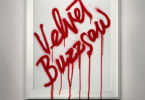 "A white frame on a wall that reads ""Velvet Buzzsaw"" in dripping red letters."