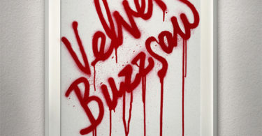 """A white frame on a wall that reads """"Velvet Buzzsaw"""" in dripping red letters."""