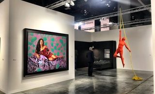 A gallery space with a large portrait and a sculptural figure holding onto a yellow rope.