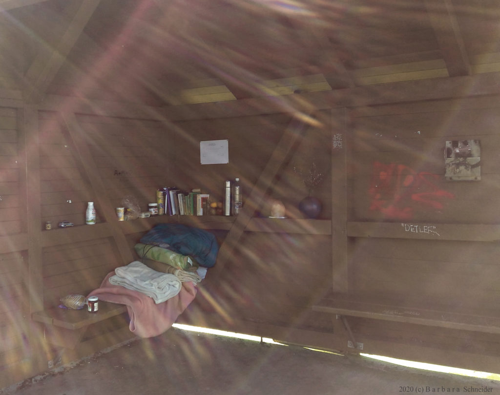 Photograph of a the inside of a rustic hut with rays of sun crossing the front of the lens.  A wooden bench is piled with bed linens, and a wooden ledge is full of books, jars and vases.