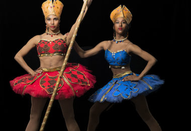 Two constumed dancers, one in a red costume and the other in blue