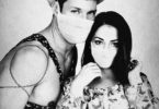 A photograph of a couple standing together wearing medial masks