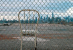 A chainlink fence - through which you see a metal hooped back white chair on a derelict empty lot, with the skyline of New York seen from Brooklyn/Queens
