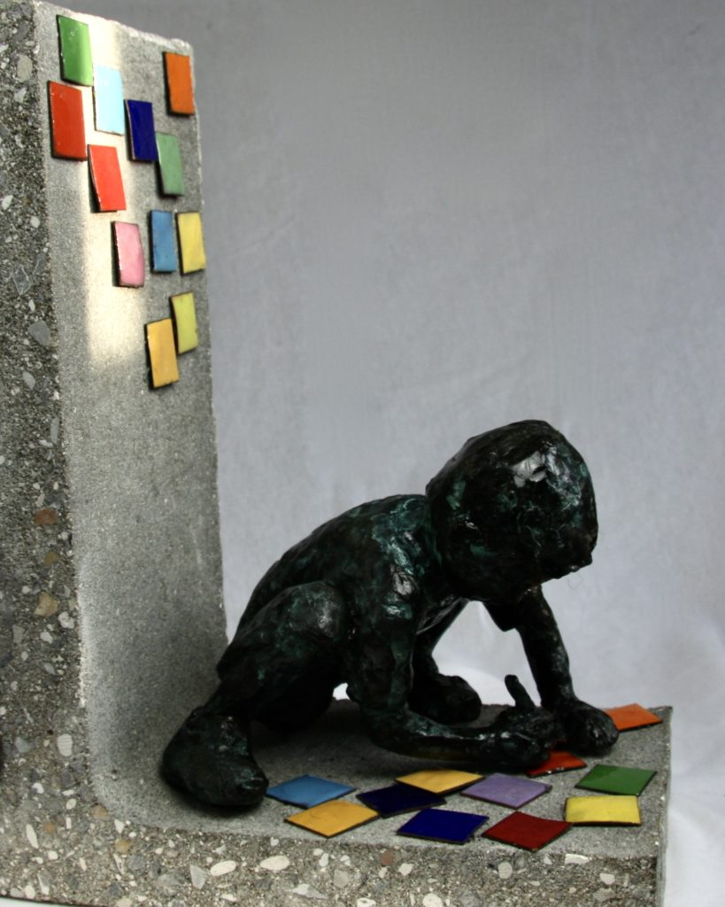 sculpture of a child writing on colored tiles sitting at the foot of a concrete wall