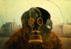 Image of a person wearing a gas mask with an idustrial background, seen through broken glass.