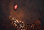 Dark abstract oil on canvas painting with a red dot