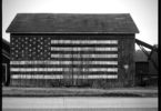 Black and white photograph of the side of a barn with an American flag painted onto it.
