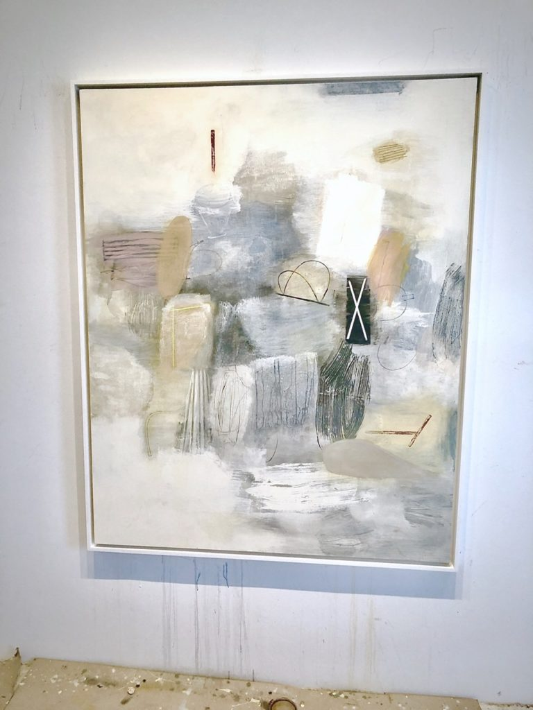 painting on a wall - an abstract of pale, grey, tan and white patches that look fluffy.  There is one black oblong with a white cross in the center of the painting with a few other random shapes and objects