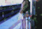 circles looking like bubbles on an opaque screen over an image of a girl standing on a train platform, overlook by another person.