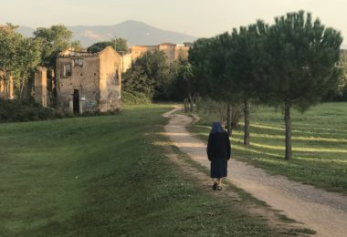 Photo of an older woman walking along a path to a village of stone buildings