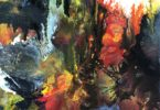 Abstract painting with splashes of color in oranges, yellow, green, brown and white.