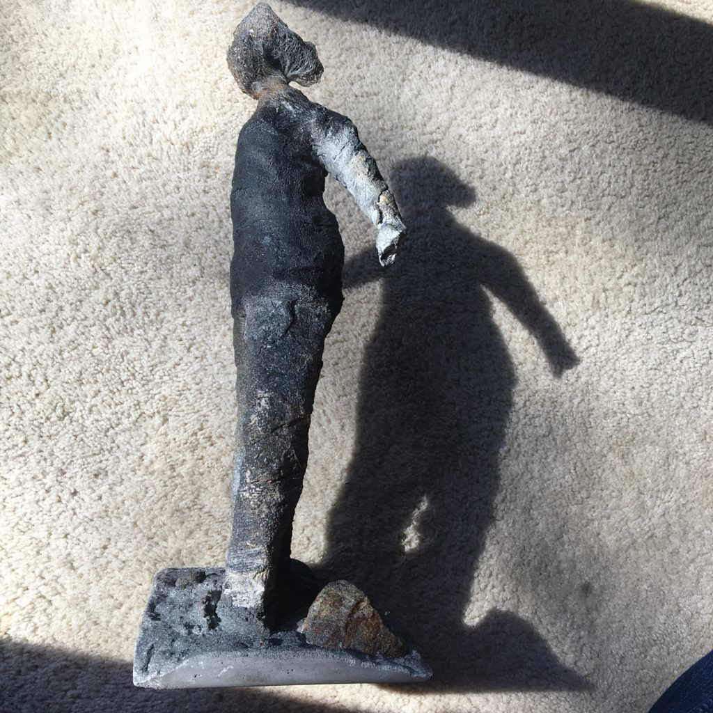 grey statue with its shadow on the wall