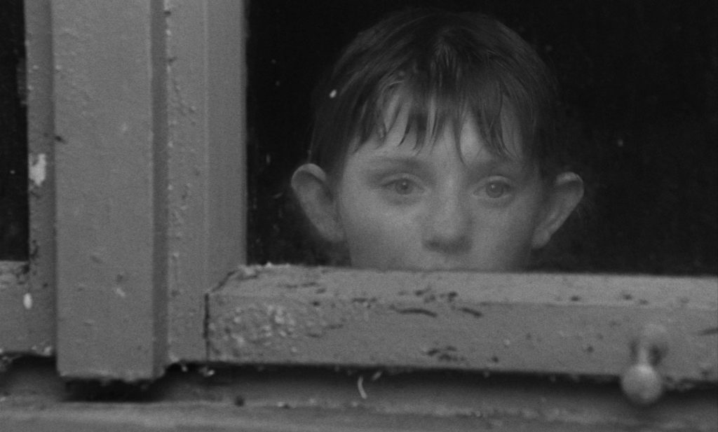 Black and white photo of a child's head, looking out a windown
