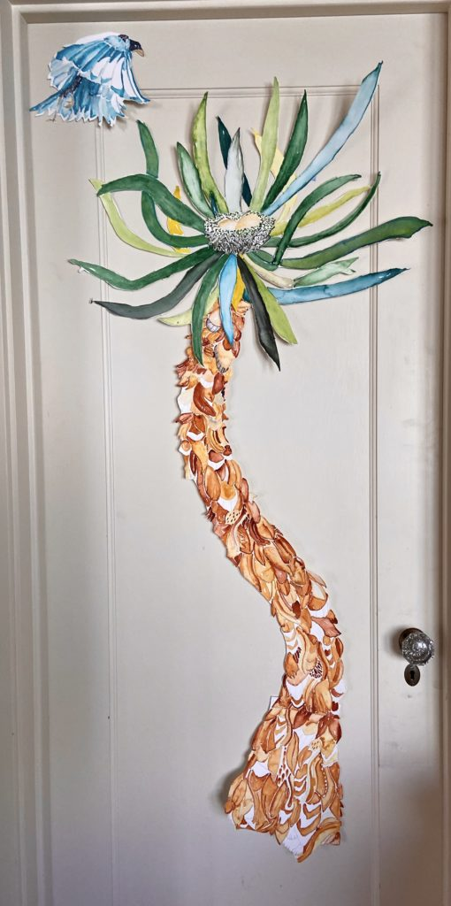 A wavy palm tree on paper with a blue bird flying above it, all hung on a door
