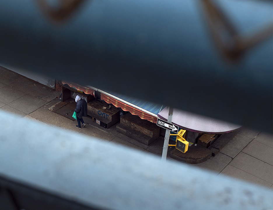photo of a person with a mint green plastic shopping bag walking in front of an empty  shop front with an awning.  The photo is taken from up high across the street through slits.  In the photo is a one way sign and a crossing signal