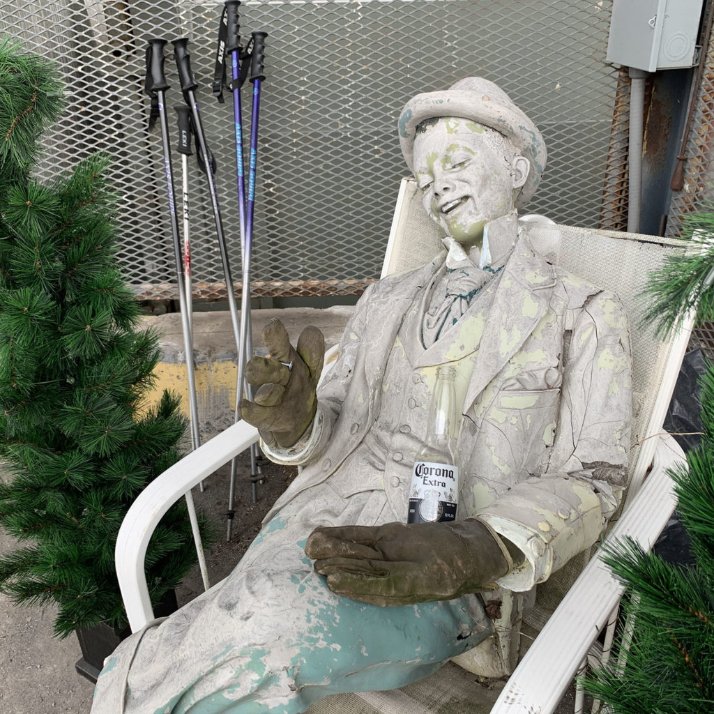 Statue of a smiling young man in a trilby hat, winter gloves and cravat lounging in a garden chair, with a bottle of corono  beer in his hand.  He is surrounded with greenery, a metal fence and ski stocks.