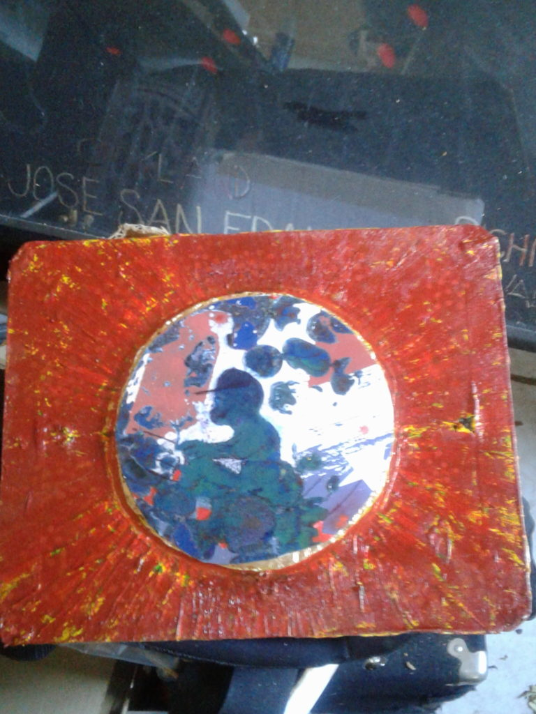 painting with a white background circle in the center of the painting with an abstract image of a person on a vehicle.  There are splashes of colors in the circle.  The outside is red and yellow radiating out from the white circle