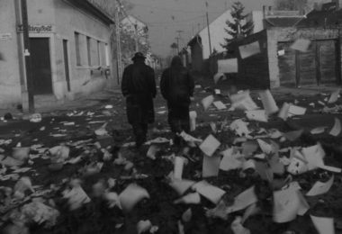 Black and white film still of two men in coats, one with a hat, walking away from the viewer, down a town street, strewn with lots of paper