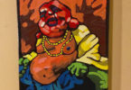 bright painting of a buddah like person with a red bald head, beaded necklae, yellow jacket, blue pants and a large belly
