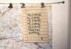 A photogrpah of piece of string tacked to the wall with hooped clips holding a map of East Berlin and a list that says my friends, my friends, my friends, my firends, my friends, road trips, swiiming, signed R