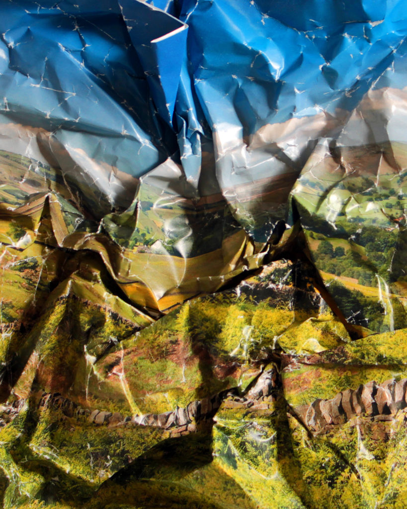 Crumpled photo paper of a green landscape, hills and blue skies