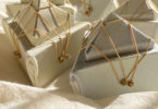 soft pyramid like origami sculptures of thick brushed material. strapped with gold string and brass pins with notted heads