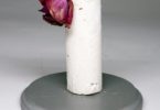 A large whtie candle like shape made of splaster stood on a flat cake stand with a red rose drooping over the top.