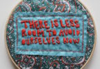 "An embroidery hoop with text that says ""There is less room to avoid ourselves now."""