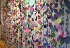 Mixed media paper circles sewn together creating a curtain.