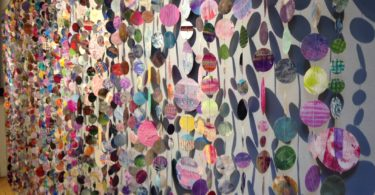 Mixed media paper circles sewn together creating a curtain.