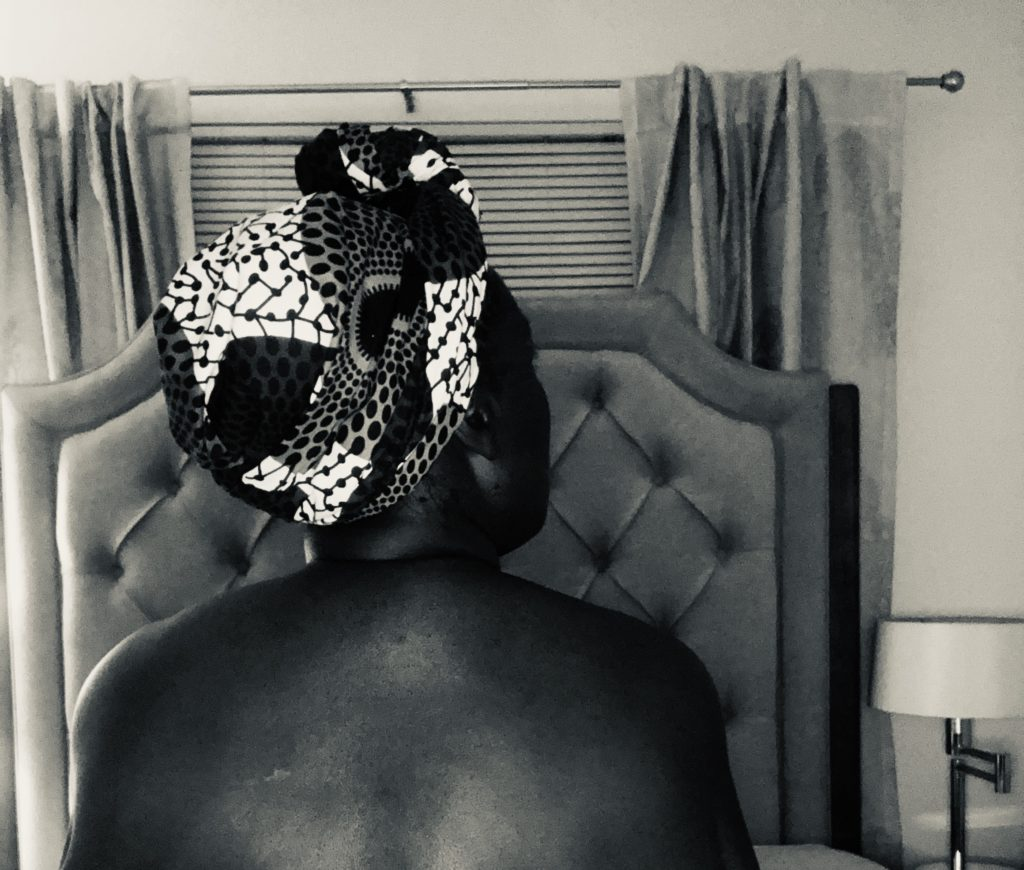 Portrait of a black woman's naked back.  Her hair is wrapped in a patterned fabric.  In the background is a headboard, window with the blinds down and drawn back curtains.  There is a stand lamp to her right