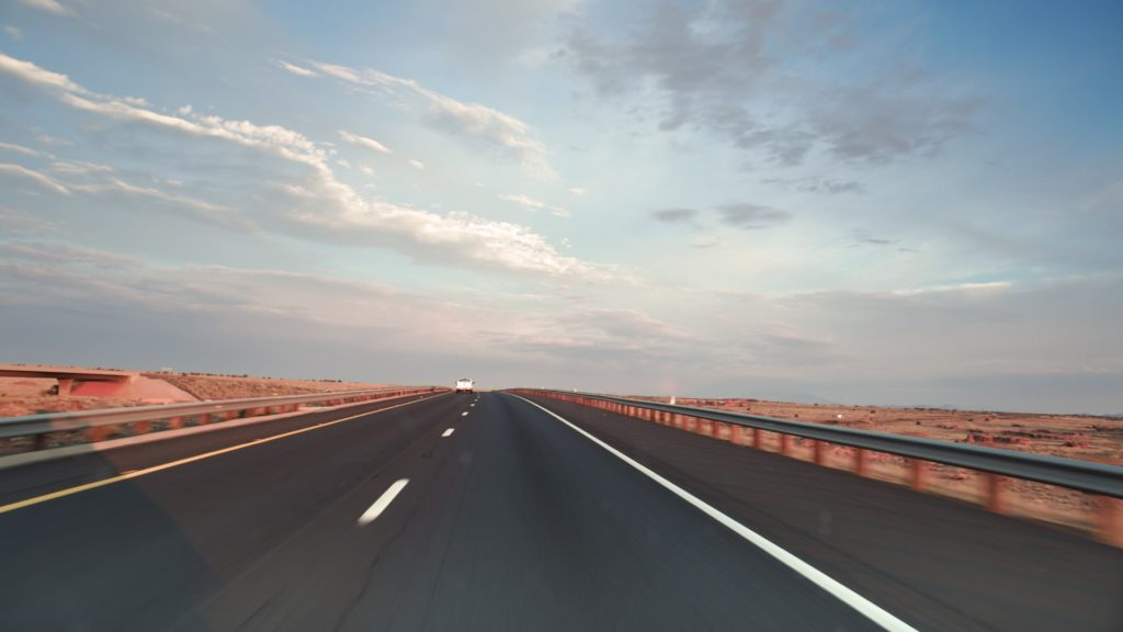 Photograph of a long straight road to the horizon with a pale blue sky with clouds.