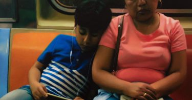 A young boy leans on a woman's shoulder while sitting on the train.