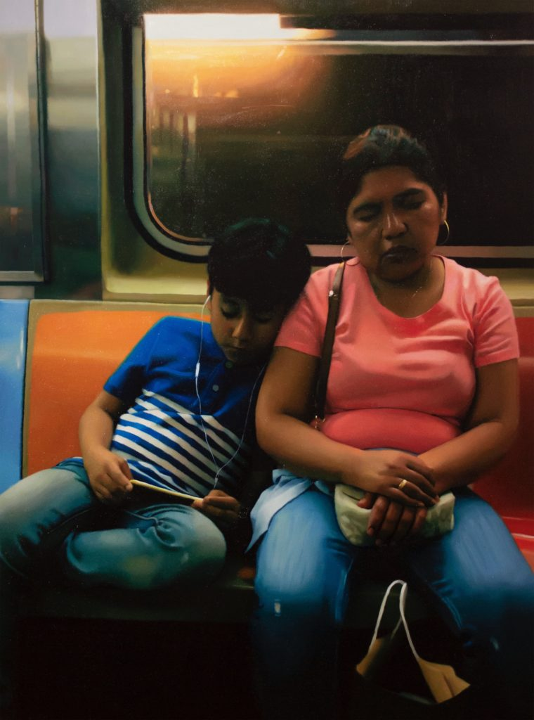 Mother and son the sitting on the subway.  The mother has her eyes closed and the boy is looking at his phone with his earphones in.