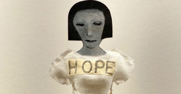 Image of a doll with a short haircut. She is dressed in a white dress with the word HOPE written across her chest