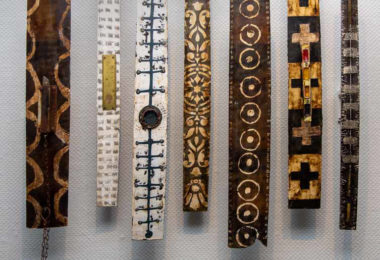 7 totem like wooden elongated rectangular pieces - laid out in a row