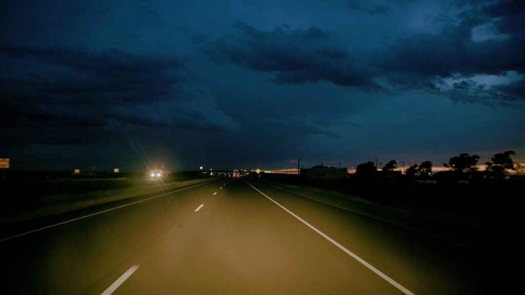 Photograph of a long straight road to the horizon as night falls and a car with headlines come toward the viewer in the left hand lane