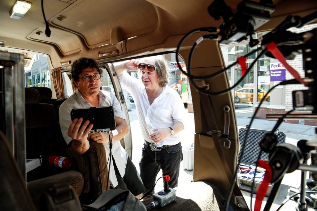 Photo of the two men by their van, showing some of the technical seup inside the van.