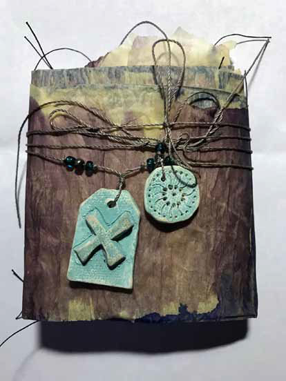 A book like assemblage wrapped in altered issue paper, tied in twine with turquoise beads and two blue objects made of clay.
