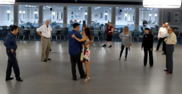 Photograph of a couple dancing with people looking on