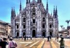 Photograph of Milan Cathedral and Piazza del Duomo. A few people stand around and pigeons are on the ground.