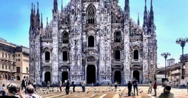 Photograph of Milan Cathedral and Piazza del Duomo. The magnificent cathedral is in the background. A few people are standing around, there are more pigeons on the ground than people. There are a few poeple with masks.