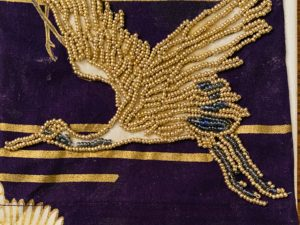 Beaded embroidered bird-like figure on a dark textile.