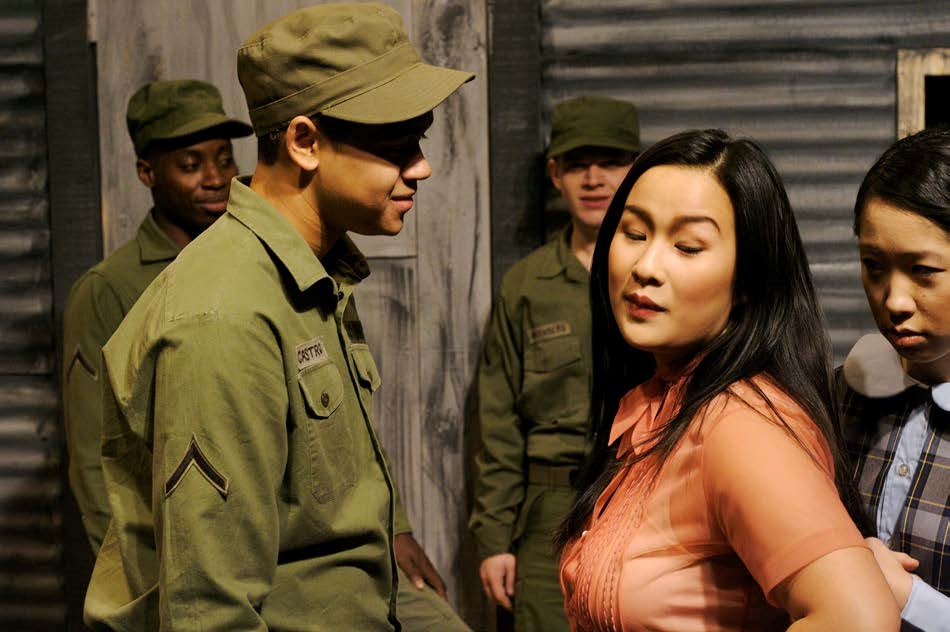 Photograph of a stage production, 3 men in army green, a young asian looking girl in a orange blouse, and a younger looking girl behind her
