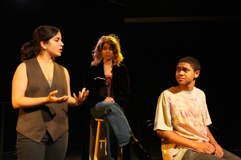 photograph of a stage production with a woman standing on the left gesticulating with her hands, a woman sat on a tall stool in the back center ad a young man in a baggy t-shirt sitting down